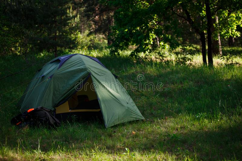 Green tourist tent stands in the woods, illuminated by rays of light. stock photo