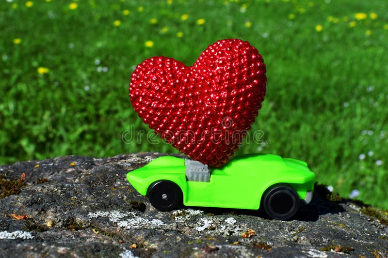 Green toy car carry red heart. On big stone on meadow background with copy space for text. Valentines day concept royalty free stock photo