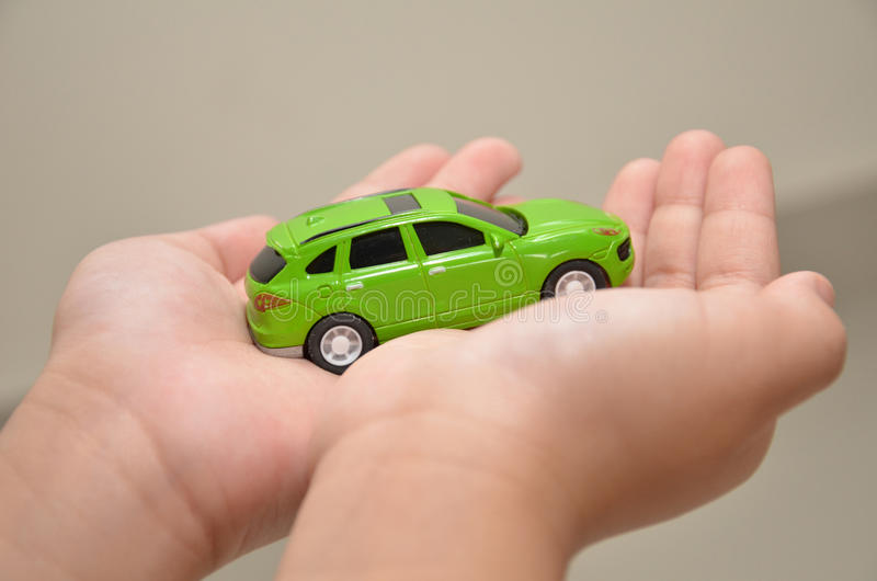 Green toy car on a right hand. With white background royalty free stock photography
