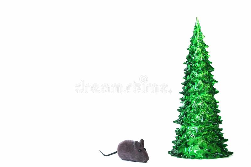 Green toy Christmas tree and toy grey mouse isolated on white background. Symbol of The new year 2020. Copy space royalty free stock photography