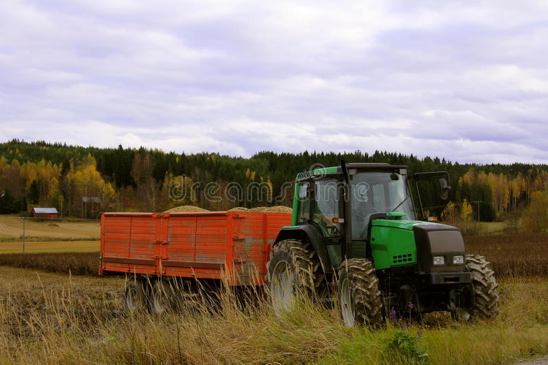 Green Tractor and Agricultural Trailer stock photo