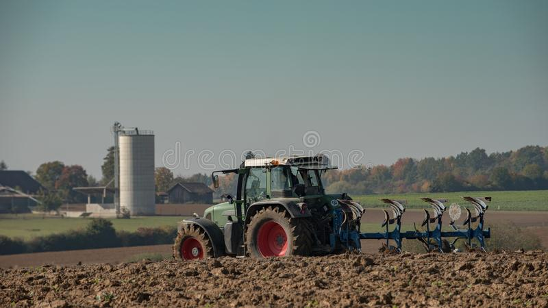 Tractor ploughing field with blurry farm in the background. Green tractor ploughing field in front of a farm in the background - Panorama shot royalty free stock photos