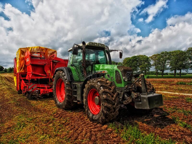 Green Tractor Pulling Red Bin On Field At Daytime Free Public Domain Cc0 Image