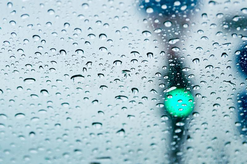 Green traffic light through the car glass in the rain drops. Close-up, selective focus. Green traffic light through the car glass in the rain drops. Closeup royalty free stock photos