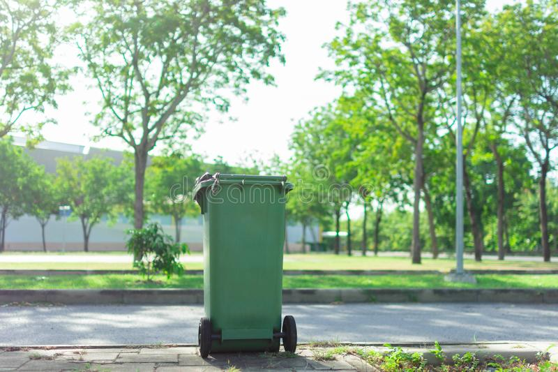 Green trash in the garden. Moulded plastic, wheeled waste bin in The park. Trash or bin is tools of Waste management. Green trash in the garden. Moulded plastic royalty free stock photography