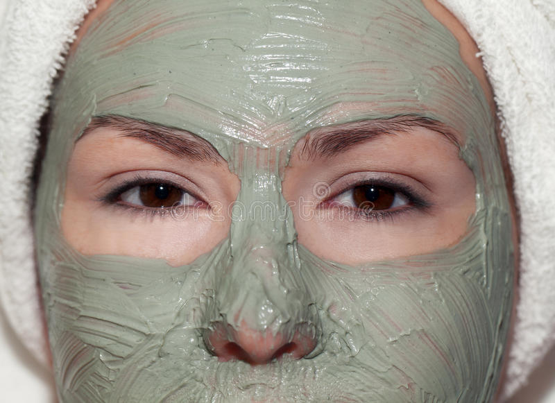 Green treatment. Young woman in green mud mask and wrapped in a tower stock photos