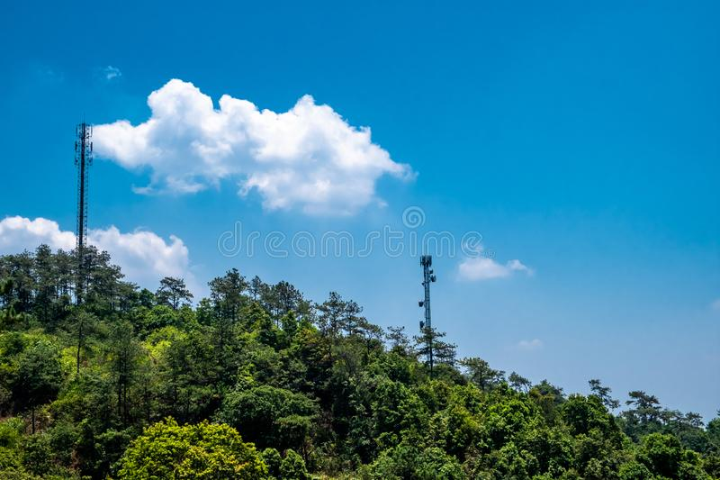 Green tree forest and telecommunication towers against clear blue sky with white fluffy clouds. royalty free stock photos