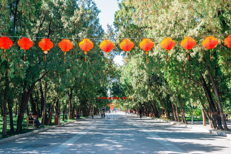 Green tree road and hanging chinese lanterns at Temple of Earth, Ditan Park in Beijing, China. Beijing, China - September 21, 2018 : Green tree road and hanging stock image