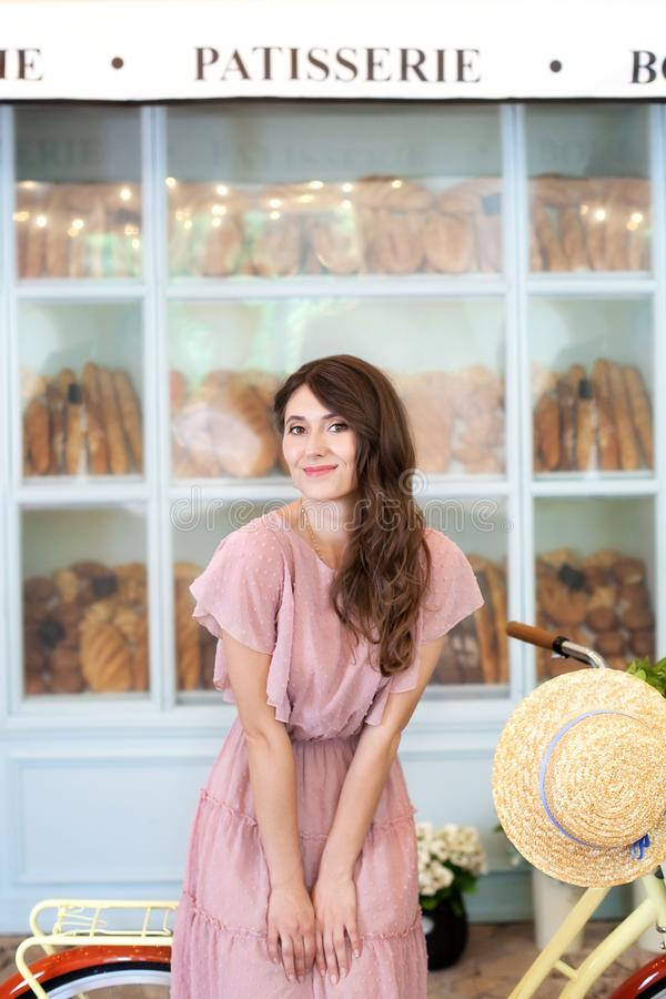 Green trip healthy concept, Eco transport. Romantic girl standing near her bike on the background of a bakery cafe. Portrait of a royalty free stock photo