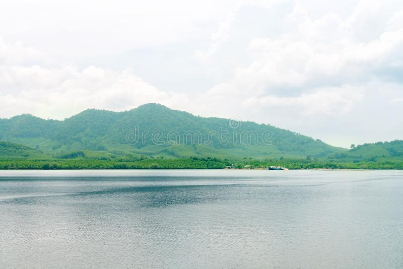 Green tropical island with calm sea and cloudy sky. Green hilly tropical island with calm sea and cloudy sky stock photo