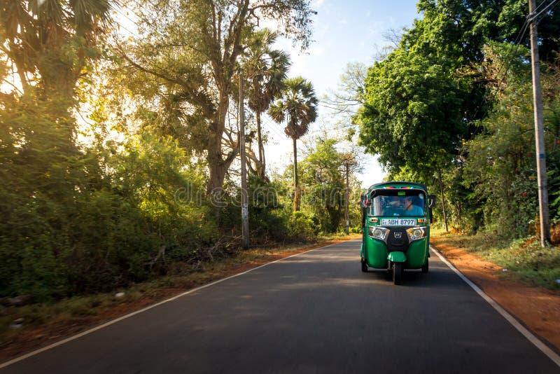 A green tuktuk rickshaw zooms through country lanes around Anu stock image