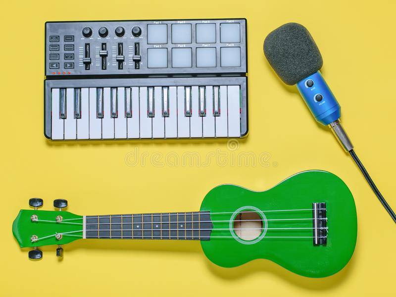 Green ukulele, blue microphone with wires and music mixer on yellow background. The view from the top. Green ukulele, blue microphone with wires and music mixer royalty free stock photography