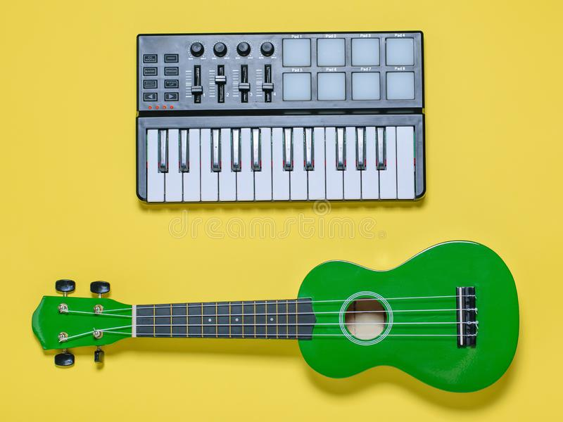 Green ukulele and music mixer on yellow background. The view from the top. Green ukulele and music mixer on yellow background. Equipment for recording music stock images