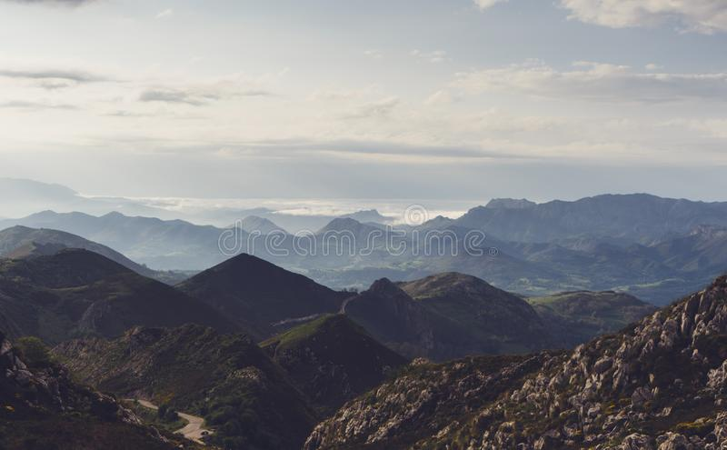Green valley on background dramatic sky and clouds. Panorama horizon view of scenery foggy hills Northern Spain alps. Travel stock photos