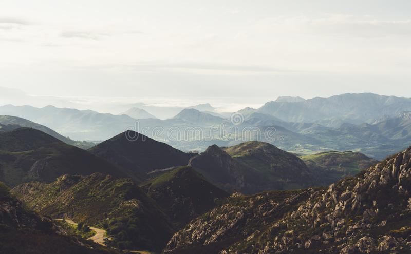 Green valley on background dramatic sky and clouds. Panorama horizon view of scenery foggy hills Northern Spain alps. Travel mock stock image
