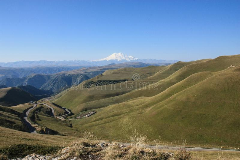 Green valley in Caucasus mountains with serpentine road and Elbrus mountain, Russia royalty free stock images