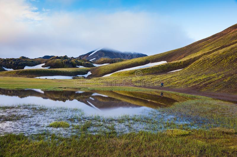 Green Valley is flooded with melt water. Early summer morning in the National Park Landmannalaugar, Iceland. Snow lies in the hollows of colorful rhyolite stock photo