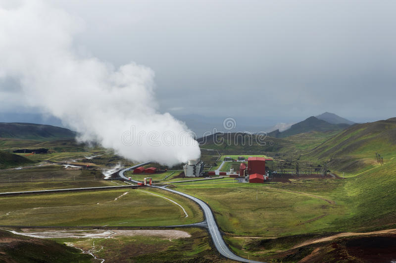 Green valley with industrial view of geothermal power station, K. Green valley with industrial view of geothermal power station and heavy clouds, Krafla, Iceland stock photo