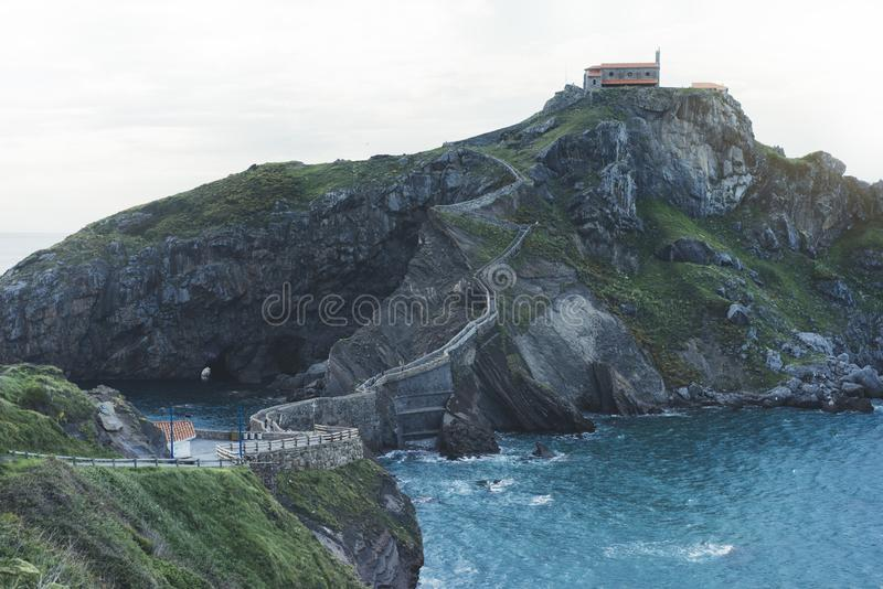 Green valley landscape on background dramatic. View sunlight blue ocean in trip holiday in basque island Gaztelugatxe. Panorama. Horizon of scenery foggy hills royalty free stock photography