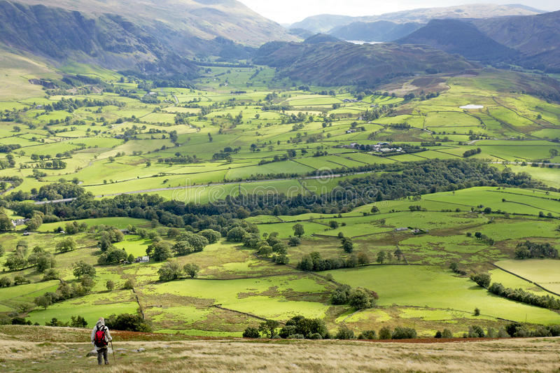 Green Valley Landscape, England. Walker descending to the rolling green fields of the Threlkeld Valley in the Lake District National Park. Cumbria, England, UK royalty free stock images