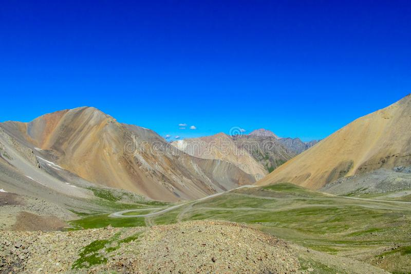 Green valley and road between colorful mountains. Green grass in summer stock photography
