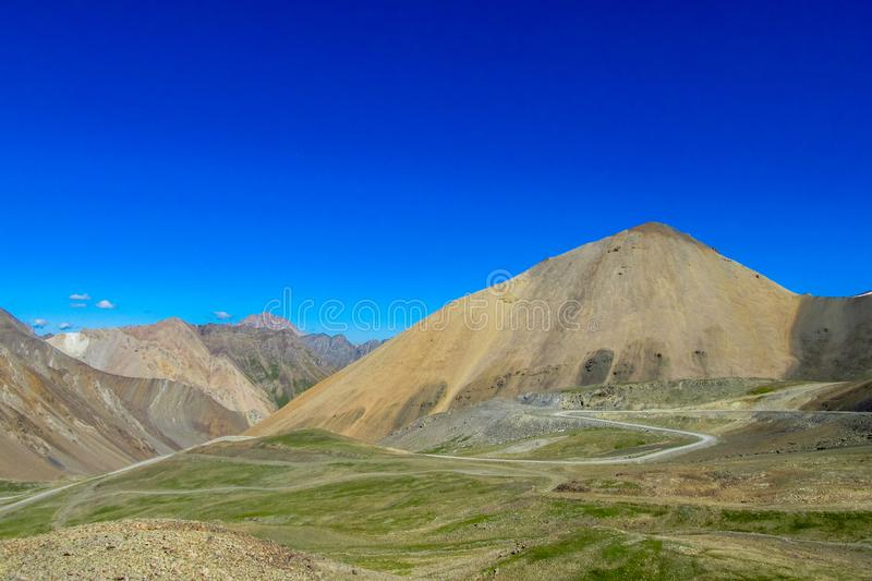 Green valley and road in Tian Shan mountains. Green valley in Tian Shan Than-Shan region in Kazakhstan and Kyrgyzstan stock photos