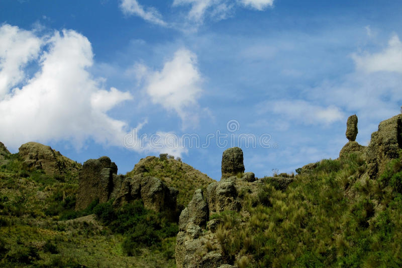Green valley and rock formations under blue sky. Valle de las Animas rock formation cliff towers near La Paz in Bolivia. Cloudy weather royalty free stock photography