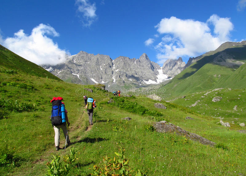 Green valley and rocky peaks of Caucasian Mountains in Georgia. People with big backpacks going for a trekking on a path through the green valley in Caucasian stock photo