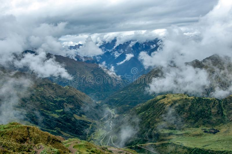 Green valley surrounded by mountains in clouds, Choquequirao trek between Yanama and Totora, Peru. Green valley surrounded by mountains in clouds, between Yanama royalty free stock photo