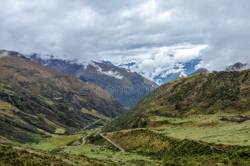 Green valley surrounded by mountains in clouds, Choquequirao trek between Yanama and Totora, Peru. Green valley surrounded by mountains in clouds, between Yanama stock photo
