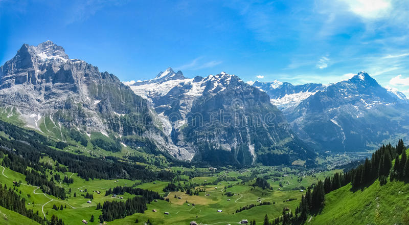 Green valley in the Swiss Alps. Small village in a green valley and at the bottom of the mountains of the Swiss Alps stock images