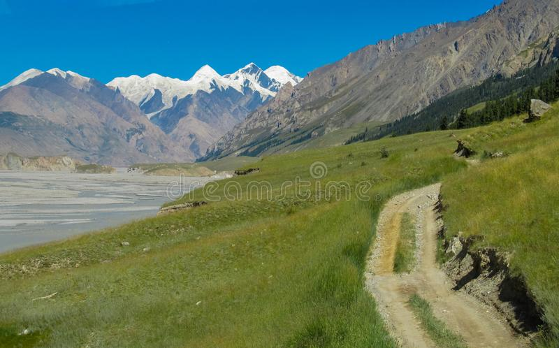 Green valley and road in Tian Shan mountains. Green valley in Tian Shan Than-Shan region in Kazakhstan and Kyrgyzstan royalty free stock photo