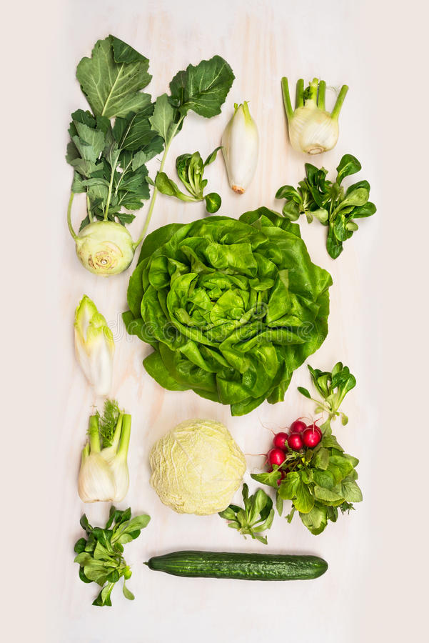 Green variety salad vegetables: lettuce,cucmber,radishes, fennel, kohlrabi on white wooden background royalty free stock photos