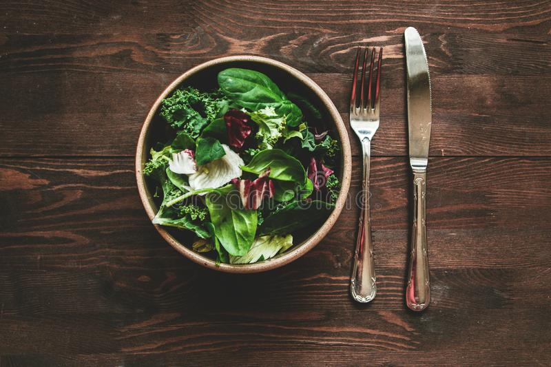 Green vegan Breakfast in a bowl with various leaves and cutlery, on wooden background, top view. Clean eating, dieting, vegan royalty free stock photo