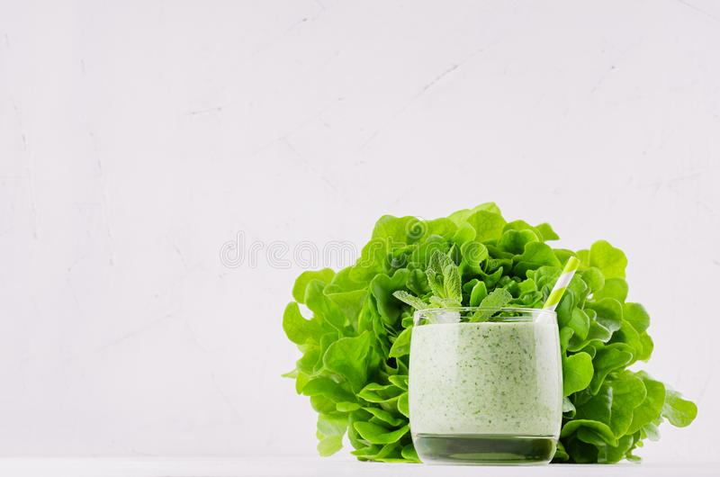 Green vegetable smoothie in glass with straw, mint twig, lettuce, copy space. Soft white wooden board background. stock photos