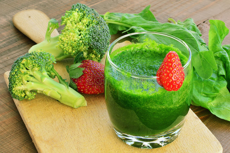 Green vegetable smoothie with strawberries. Spinach, broccoli, cucumber smoothie in glass stock photo