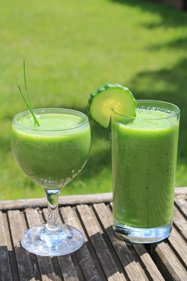 Green vegetable smoothies. Green vegetable healthy smoothies with cucumber and chive relish, outside on the garden decking royalty free stock images