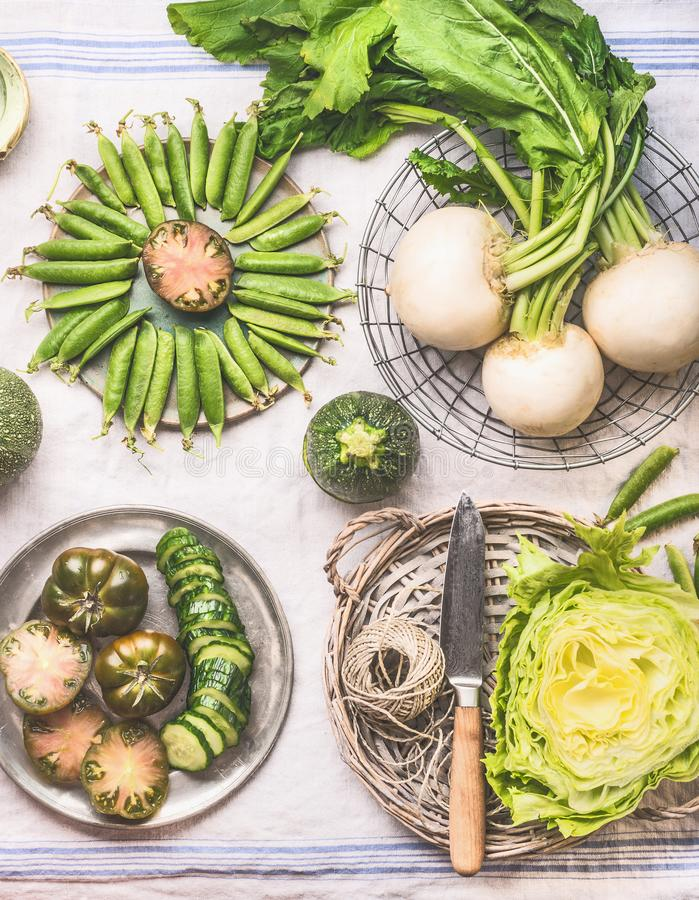 Green vegetables in bowls on light table with knife: green peas, kohlrabi, lettuce, zucchini, cucumber, green tomatoes. Top view. stock image