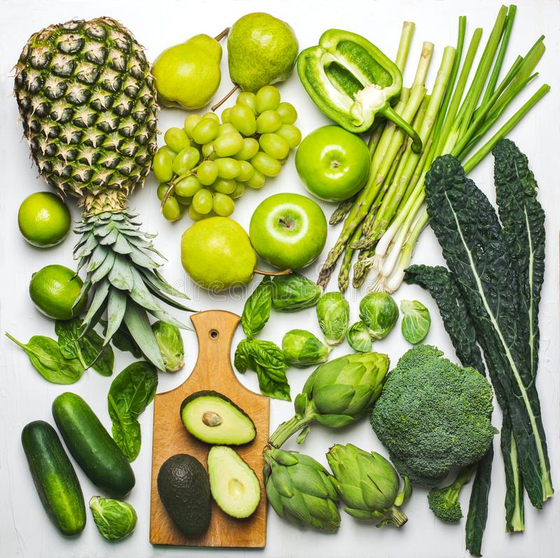 Green vegetables and fruits on a white background. Fresh organic produce royalty free stock photos