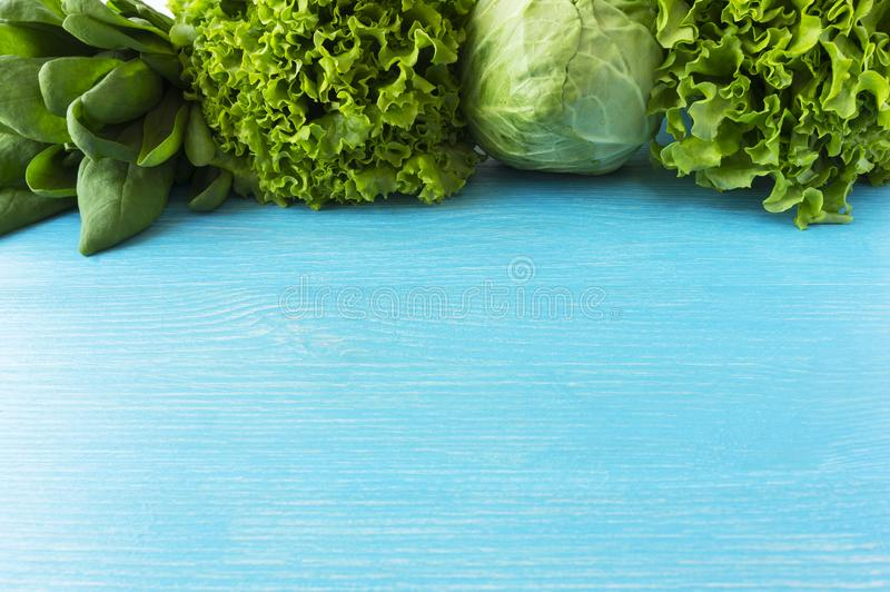 Green vegetables. Green vegetable on blue wooden background. Spinach, cabbage and lettuce. Top view. Vegetables at border of image royalty free stock images