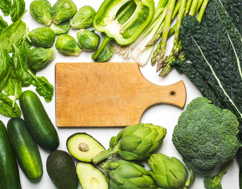 Green vegetables and herbs assortment around wooden cooking board. stock photography