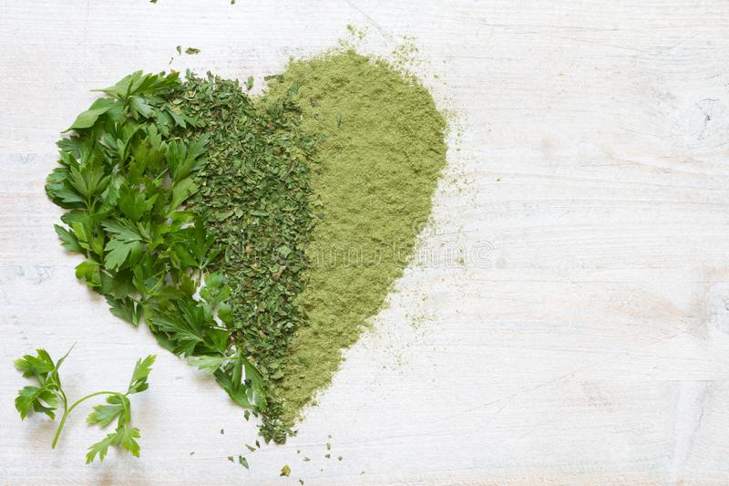 Green vegetables and herbs in heart health concept. Art stock photography