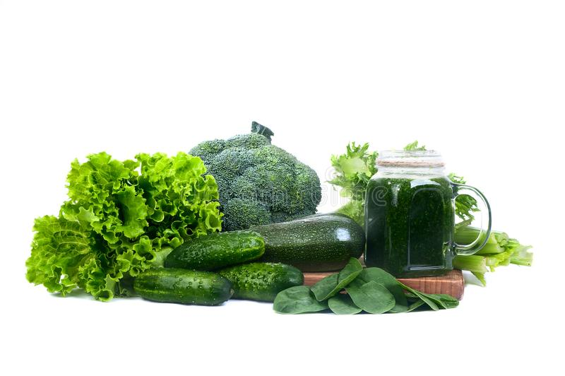 Green vegetables and smoothies from vegetables isolated. Salad, broccoli, spinach, celery. Glass with green smoothies royalty free stock photos