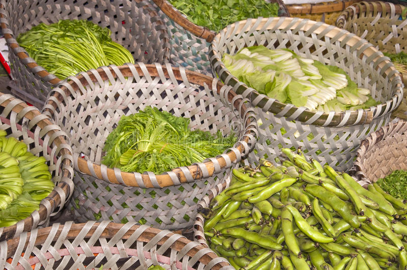 Green vegetables in straw basket stock photo