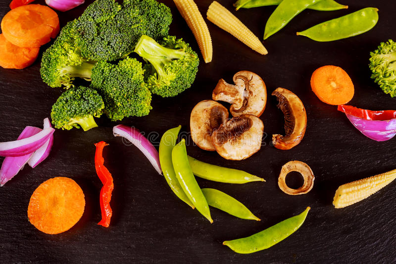 Green vegetables on the table made of black stone stock photography