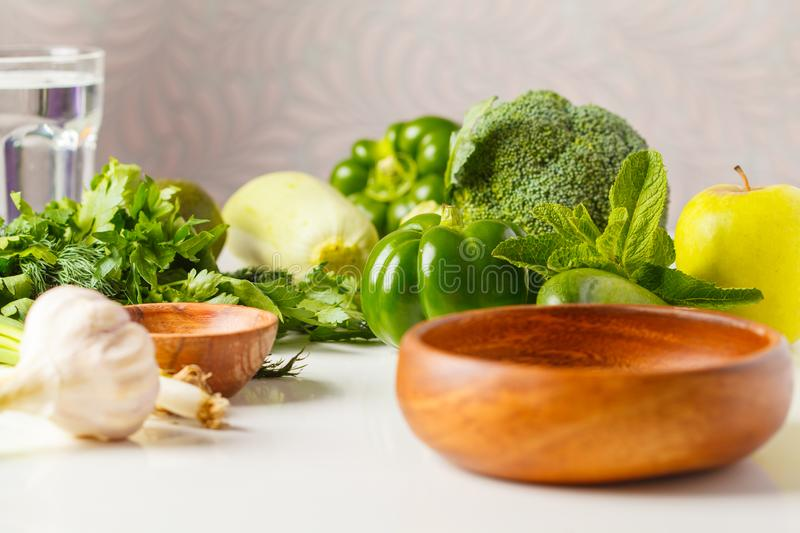Green vegetables on table. Vegetable vegan diet food background: zucchini, peppers, broccoli, cucumbers, avocado, apple, herbs. H stock image