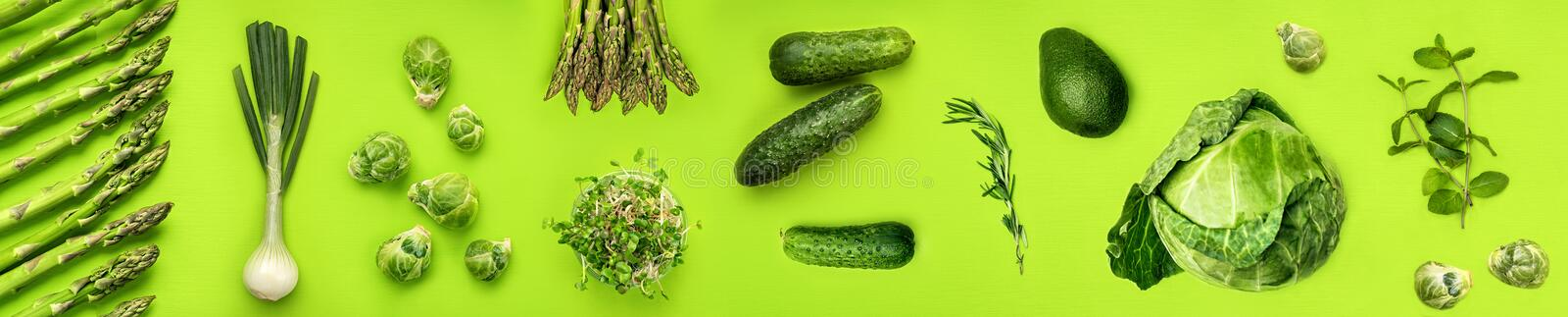 Wide green vegetables flat lay concept on green background stock image