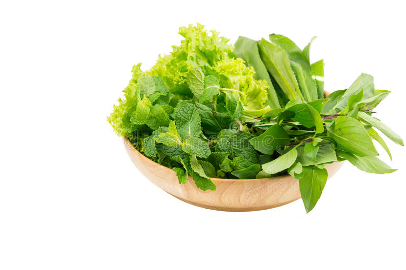 Green vegetables in wooden plate on white isolated background stock photography