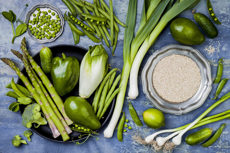 Green veggies group. Vegetarian dinner ingredients with quinoa. Green vegetables variety. Overhead, flat lay. Top view stock photography