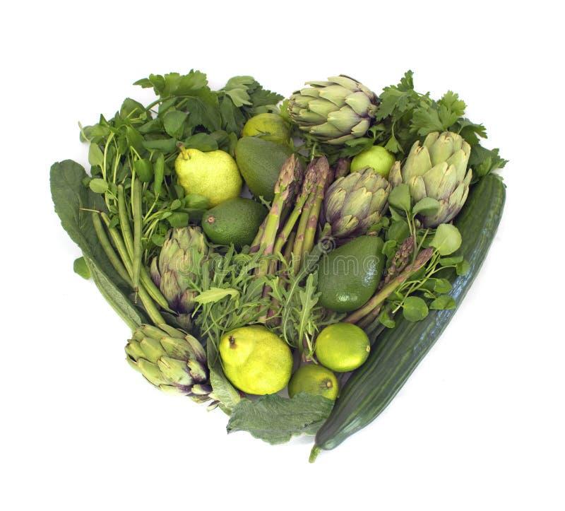 Green veggies heart on white. Big heart made of green veggies isolated on white stock image